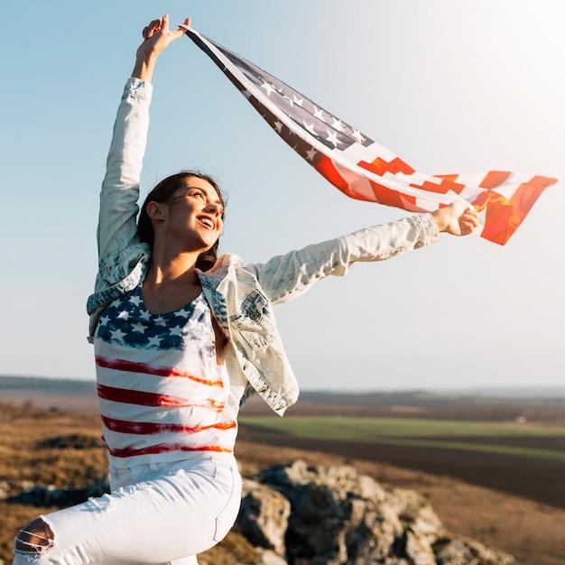 Jeune femme tenant agitant le drapeau de l'amérique Photo gratuit