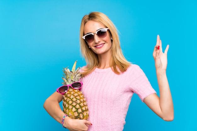 Jeune femme tenant un ananas avec des lunettes de soleil Photo Premium