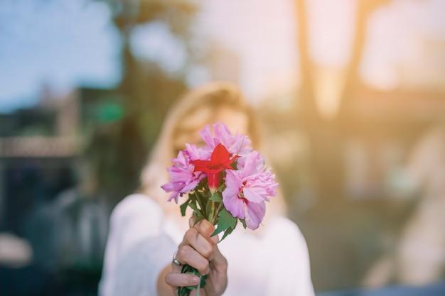 Jeune femme, tenant, bouquet fleurs, devant, elle, visage, contre, arrière-plan flou Photo gratuit