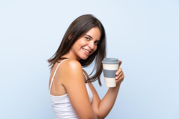 Jeune femme tenant un café à emporter sur un mur bleu isolé Photo Premium