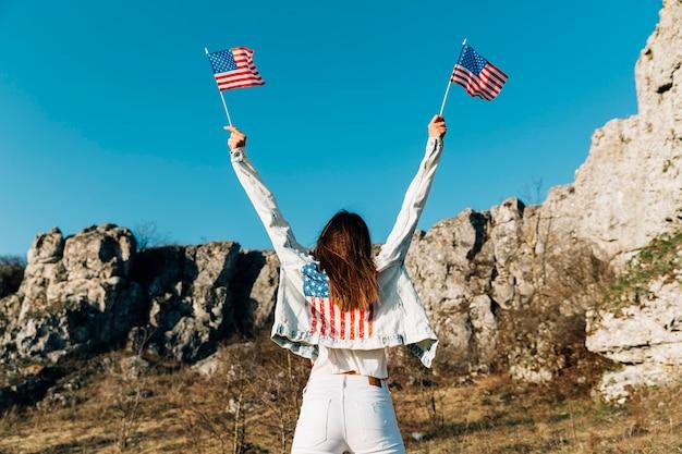 Jeune femme tenant des drapeaux américains au-dessus de la tête Photo gratuit