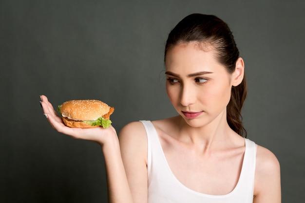 Jeune femme tenant un hamburger sur fond gris Photo Premium