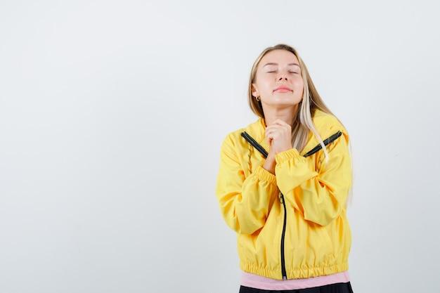 Jeune Femme Tenant Les Mains Jointes Près De La Poitrine En T-shirt, Veste Et à La Recherche D'espoir Photo gratuit