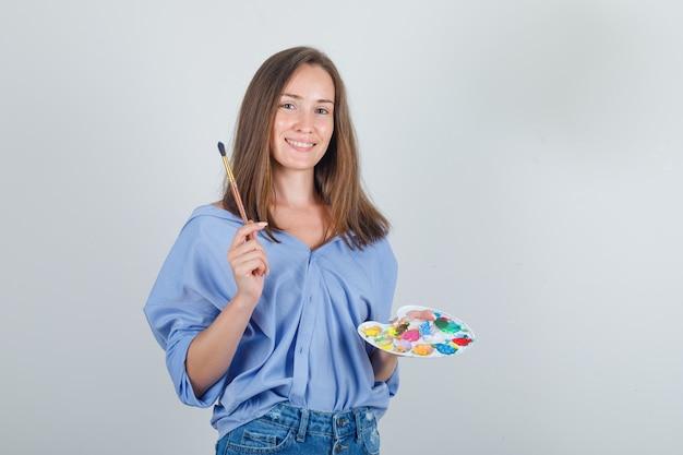 Jeune Femme Tenant Un Pinceau Et Une Palette En Chemise Bleue, Un Short Et à L'optimiste Photo gratuit