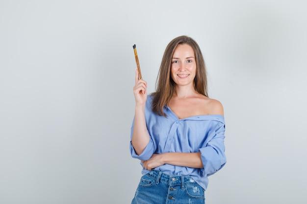 Jeune Femme Tenant Des Pinceaux En Chemise, Short Et à La Joyeuse Photo gratuit