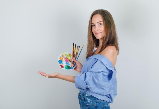 Jeune Femme Tenant Des Pinceaux Et Palette En Chemise, Short Et à La Joie Photo gratuit