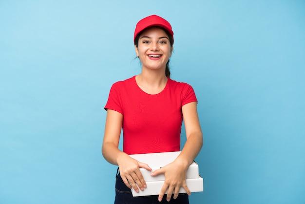 Jeune femme tenant une pizza sur un mur rose isolé avec une expression faciale surprise Photo Premium