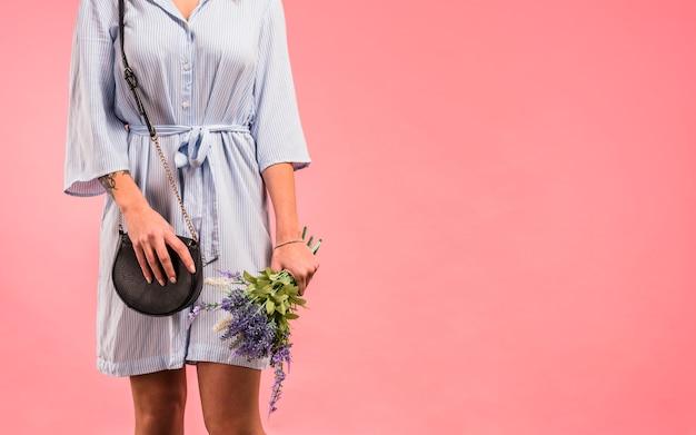 Jeune femme tenant une pochette et des fleurs Photo gratuit