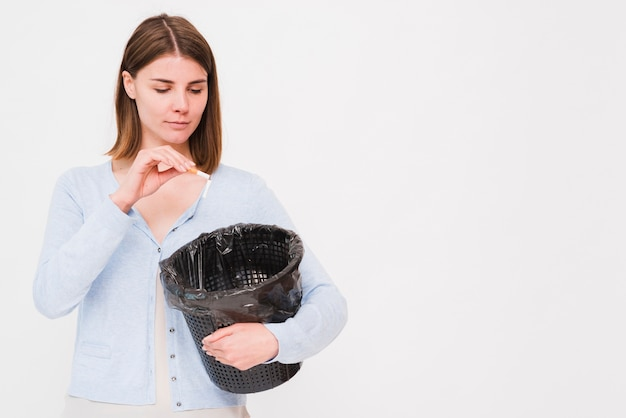Jeune femme tenant une poubelle et jetant une cigarette Photo gratuit