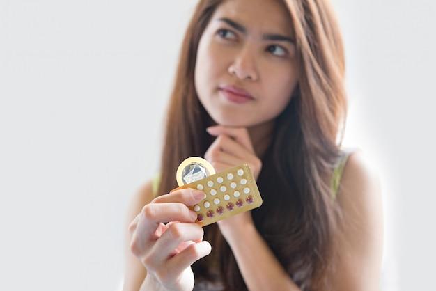 Une jeune femme tenant un préservatif et des pilules contraceptives empêche la grossesse Photo gratuit