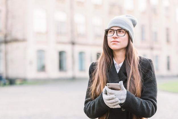 Jeune femme tenant un smartphone dans la rue Photo gratuit
