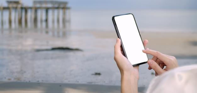Jeune Femme Tenant Un Smartphone écran Blanc Avec Fond De Plage Photo Premium