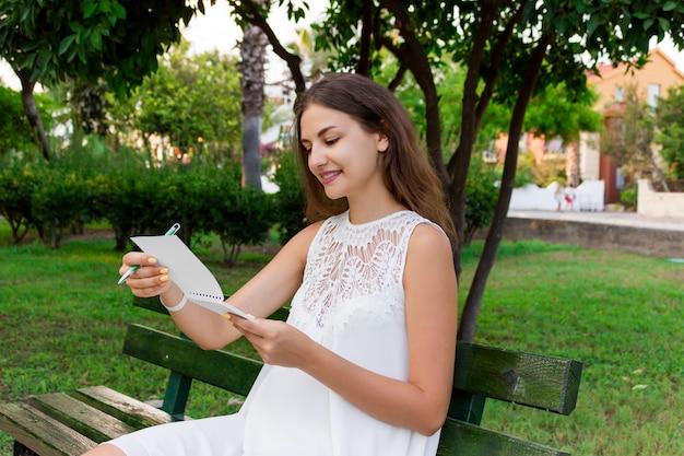 Jeune femme tenant un stylo et un bloc-notes et vérifiant son emploi du temps, ses idées et ses pensées, posant à l'extérieur Photo Premium