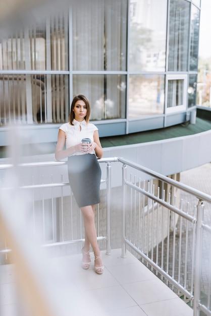 Jeune femme tenant une tasse de café debout sur le balcon Photo gratuit