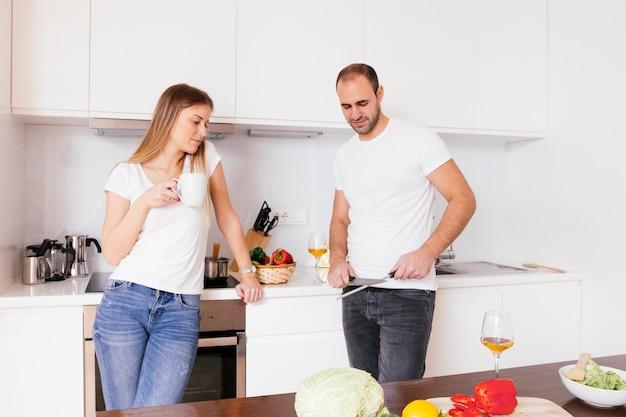 Jeune femme tenant une tasse de café à la main en regardant son mari aiguisant le couteau Photo gratuit