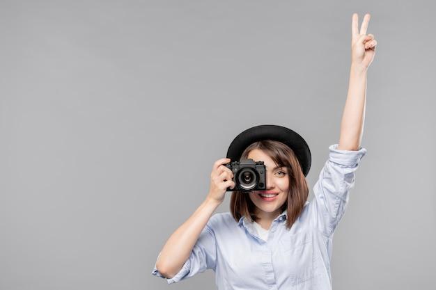 Jeune Femme En Tenue Décontractée Intelligente Montrant Le Geste De Paix Tout En Prenant Une Photo à La Caméra Photo Premium