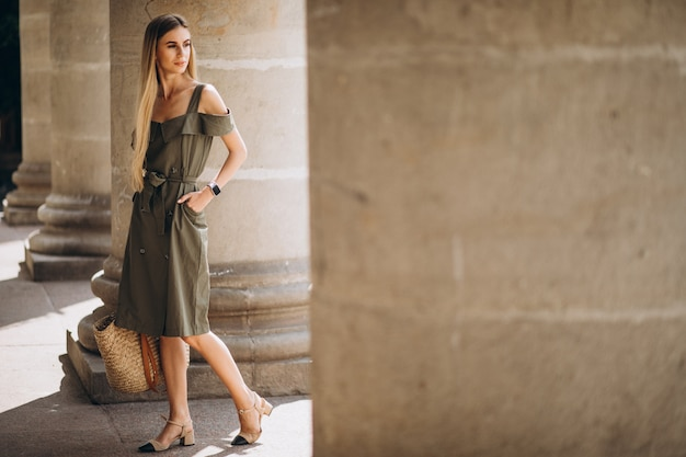 Jeune femme en tenue d'été près d'un immeuble ancien Photo gratuit