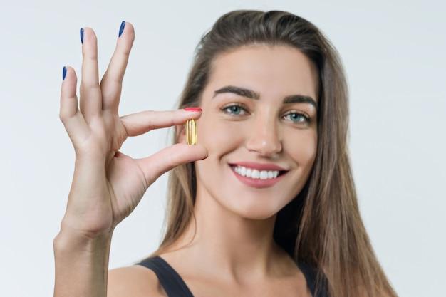 Jeune femme en tenue de sport avec vitamine d, e, a Photo Premium