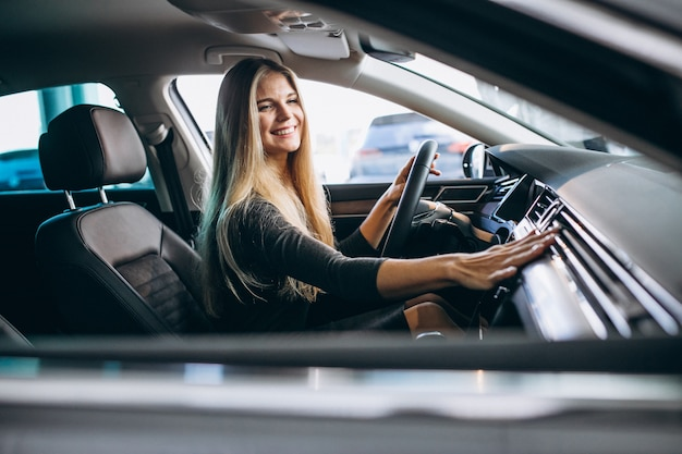 Jeune femme teste une voiture dans une salle d'exposition Photo gratuit