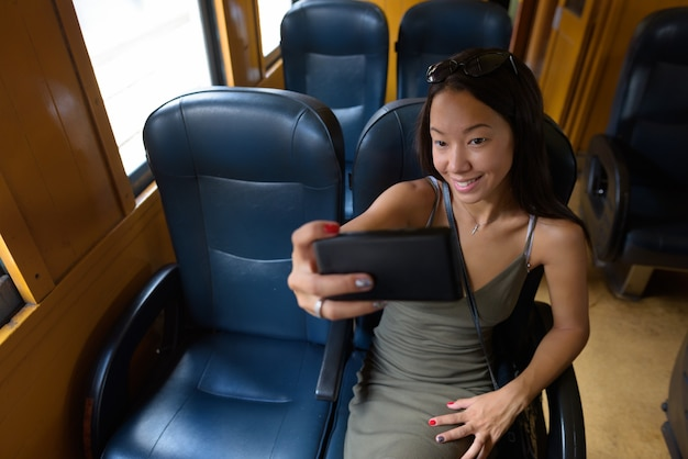 Jeune Femme De Tourisme Assis Au Train Tout En Utilisant Le Téléphone Photo Premium