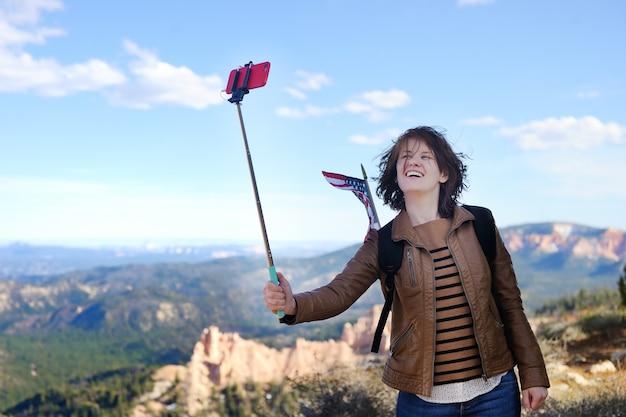 Jeune femme touriste prenant une photo d'elle-même avec un selfie à bryce canyon national park, utah, usa Photo Premium