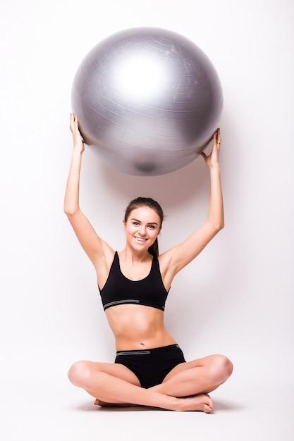 Jeune Femme Travaillant Avec Un Ballon Isolé Sur Un Mur Blanc Photo gratuit