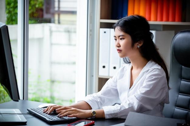 Jeune femme travaillant sur un clavier Photo gratuit