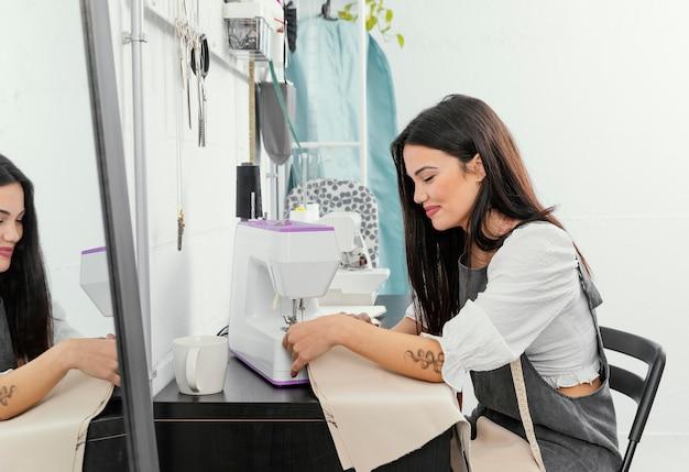 Jeune Femme Travaillant Dans Son Atelier De Design De Mode Photo gratuit