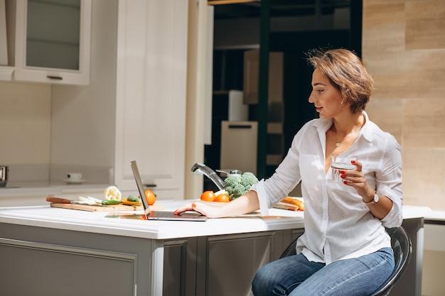 Jeune femme travaillant sur un ordinateur à la cuisine Photo gratuit