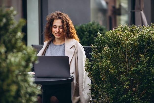 Jeune femme travaillant sur un ordinateur devant le café Photo gratuit