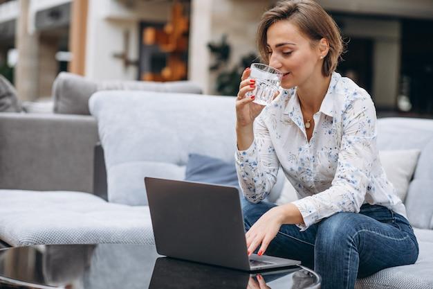 Jeune femme travaillant sur un ordinateur à la maison Photo gratuit
