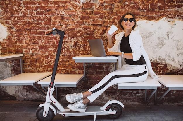 Jeune femme travaillant sur un ordinateur portable dans un café Photo gratuit