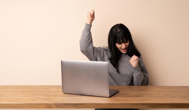 Jeune femme travaillant avec son ordinateur portable célébrant une victoire Photo Premium