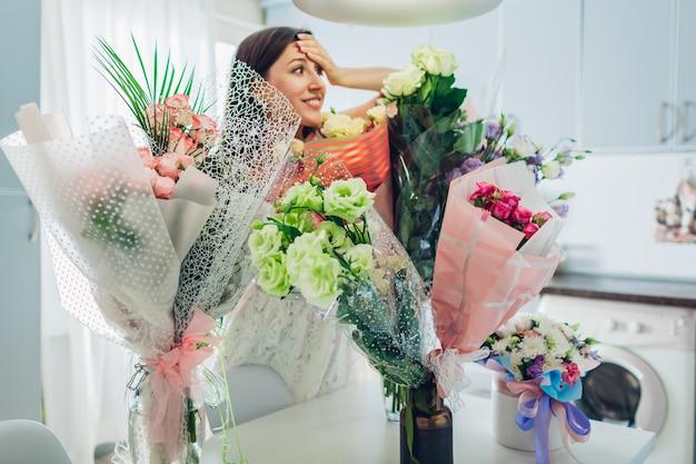 La jeune femme a trouvé beaucoup de bouquets de fleurs dans la cuisine. heureuse fille excitée souriante Photo Premium