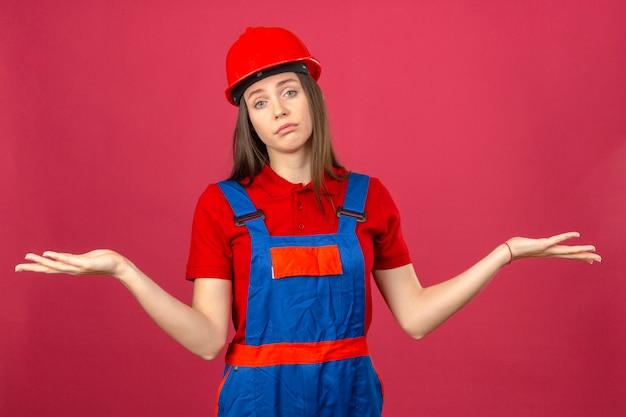 Jeune Femme En Uniforme De Construction Et Casque De Sécurité Rouge Désemparé Et Expression Confuse Avec Les Bras Et Les Mains Levées Debout Sur Fond Rose Foncé Photo gratuit