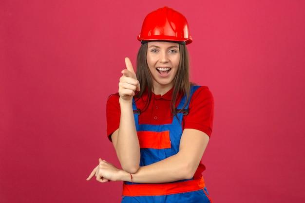 Jeune Femme En Uniforme De Construction Et Casque De Sécurité Rouge Souriant Et Heureux Regardant La Caméra Debout Sur Fond Rose Foncé Photo gratuit