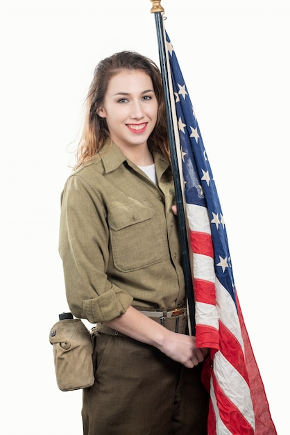 Jeune Femme En Uniforme Militaire Américain Brandissant Un Drapeau Américain. Photo Premium