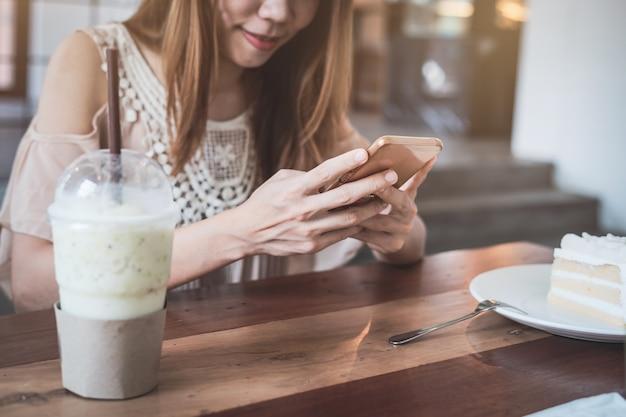 Jeune femme, utilisation, smartphone, manger, gâteau, café, vie femme Photo Premium