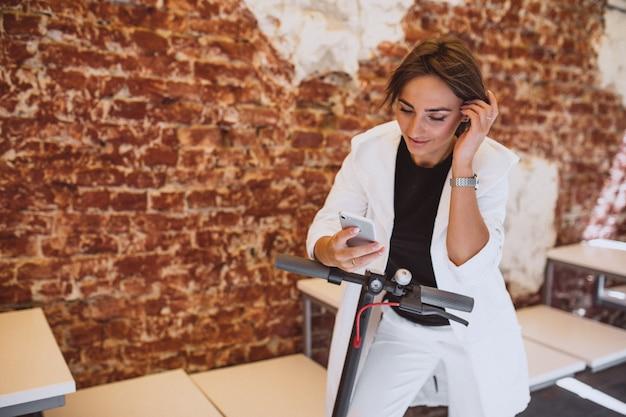 Jeune Femme, Utilisation, Téléphone, Et, Conduite, Sur, Scotter Photo gratuit