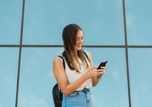 Jeune femme utilise son smartphone, il y a un miroir derrière elle Photo Premium
