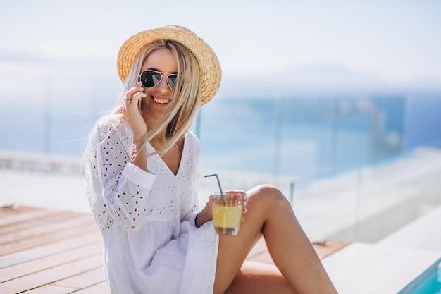 Jeune femme en vacances au bord de la piscine avec téléphone Photo gratuit