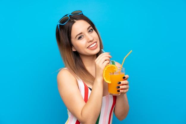 Jeune femme en vacances d'été sur mur bleu avec cocktail Photo Premium