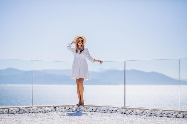 Jeune femme en vacances regardant la mer Photo gratuit