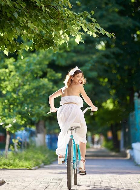 Jeune femme à vélo dans les rues de la ville Photo Premium