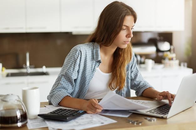 Jeune Femme Vérifiant Son Budget Et Faisant Des Impôts Photo gratuit