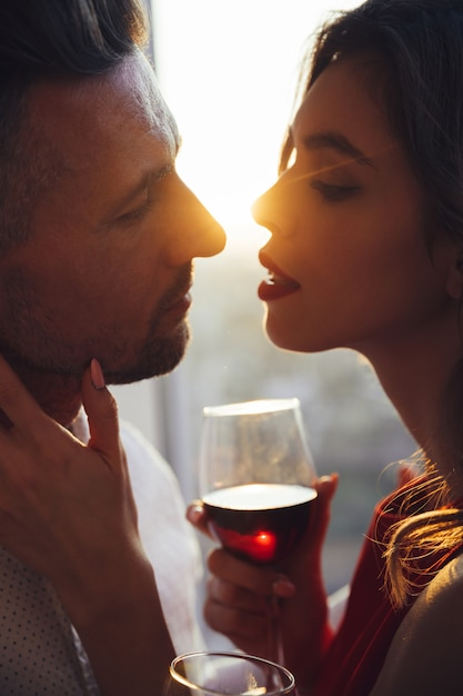 Jeune Femme Avec Verre De Vin Embrassant Son Homme Au Coucher Du Soleil Photo gratuit