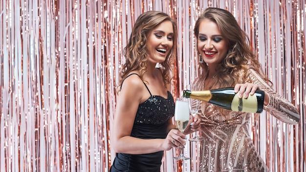 Jeune Femme Versant Du Champagne Dans Les Verres. Photo Premium