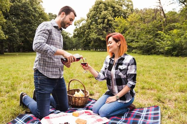 Une jeune femme versant du vin dans un verre tenir par sa femme à un pique-nique dans le parc Photo gratuit