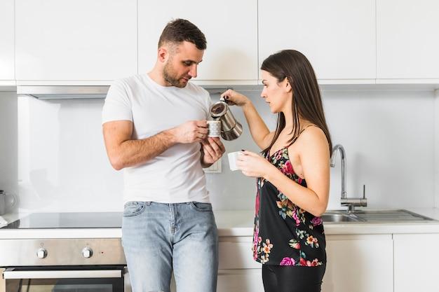 Jeune femme, verser, café, tasse, tenir, petit ami Photo gratuit