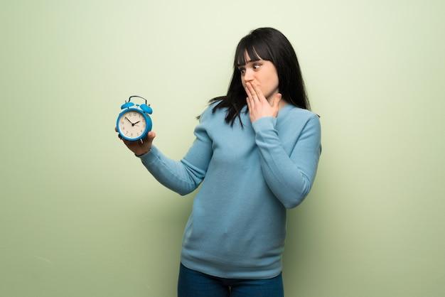 Jeune femme, sur, vert, mur, tenue, réveil vintage Photo Premium